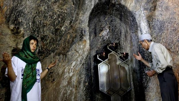 Zoroatristen beten an einem Schrein in einer Berghöhle.