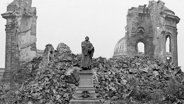 Eine zerstörte Kirche, im Vordergrund eine unversehrte Statue.