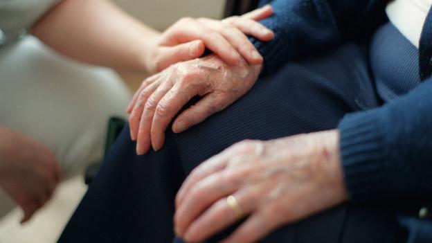 Eine Pflegerin hält die Hand einer Seniorin in einem Schweizer Pflegeheim.