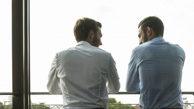 Zwei Männer stehen an einem Fenster.