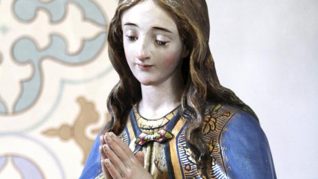 Eine Mariastatue mit gefalteten Händen.