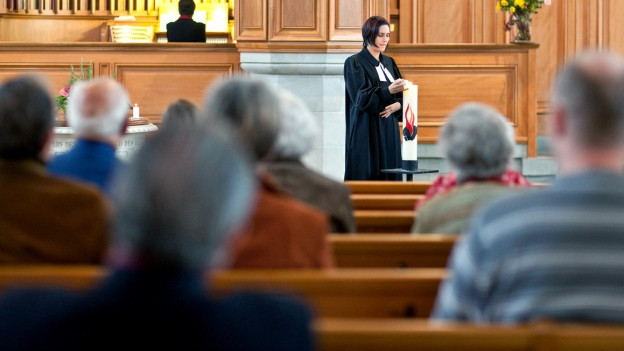 Eine Pfarrerin zündet während einer Messe eine Kerze an.