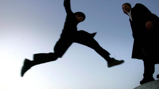 Eine Jude im Luftsprung, ein zweiter steht daneben.