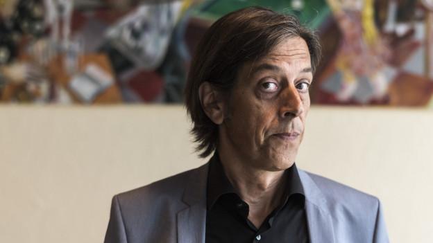 Ein Mann mit halblangem Haar und kritischem Blick.