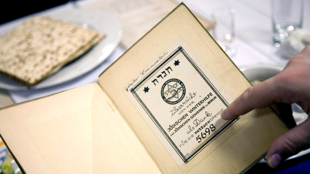 Eine Hand zeigt in ein aufgeschlagenes Buch mit hebräischen Schriftzeichen. Im Hintergrund ist ein gedeckter Tisch sichtbar.