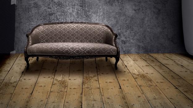 Ein antikes Sofa auf einem Holzboden, dahinter eine Wand.