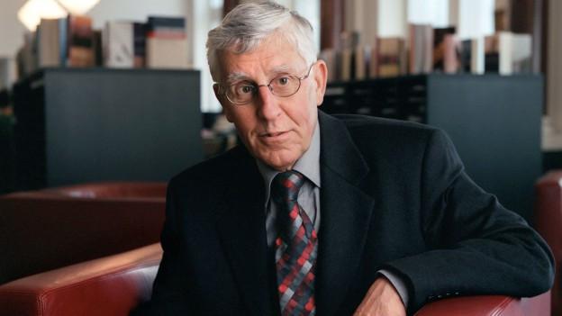 Ein Mann in Anzug und Krawatte sitzt auf einem Ledersofa.
