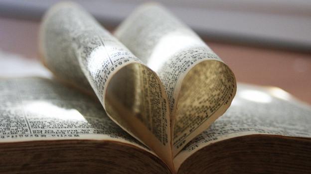 Eine Bibel ist so aufgeschlagen, dass die Seiten in der Mitte ein Herz bilden.