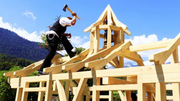 Ein Zimmermann arbeitet an einem Dachgerüst.