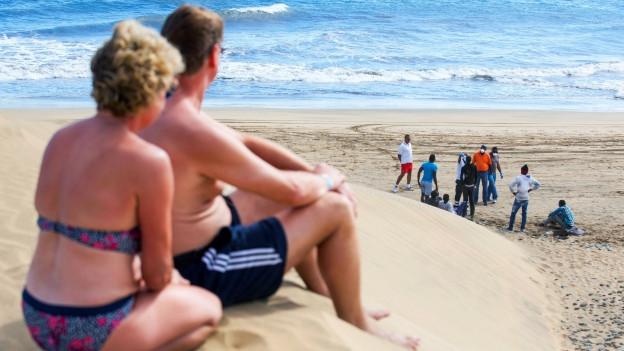 Zwei Touristen sehen von einer Sanddüne aus ankommende Flüchtlinge am Strand.