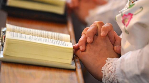 Geöffnetes Gesangsbuch und gefaltete Hände einer Person, die wahrscheinlich daraus singt.