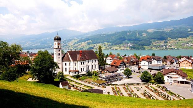 Foto eines Dorfes am See, in der Mitte ein Kirche.