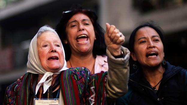 Drei Frauen, eine davon älter und mit einem weissen Kopftuch, schreien Parolen an einer Demonstration.
