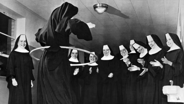 Schwarz-Weiss Foto von Nonnen, die in einem Kreis stehen und lachend einer anderen Nonnen mit Hulahop-Reifen zuschauen.