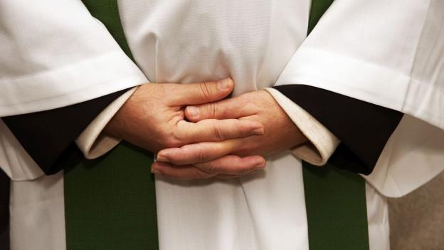 Foto von gefaltenen Hände eines Priesters.