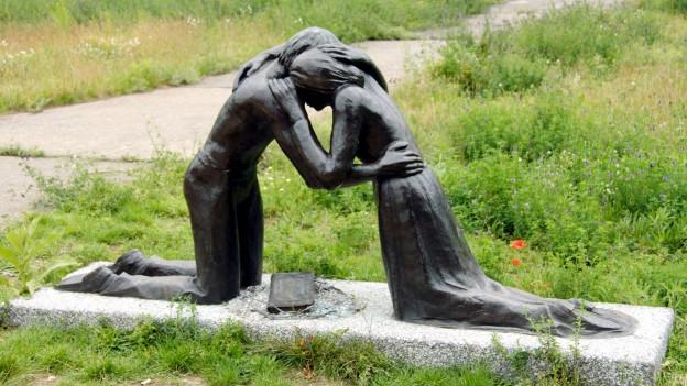 Ein Denkmal von einem Mann und einer Frau aus Bronze, die sich auf Knien innig umarmen