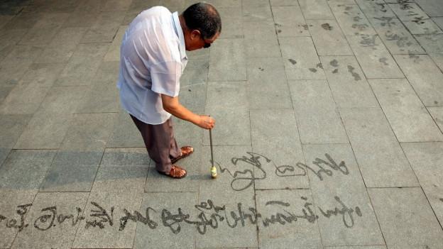 Ein Mann schreibt auf dem Boden
