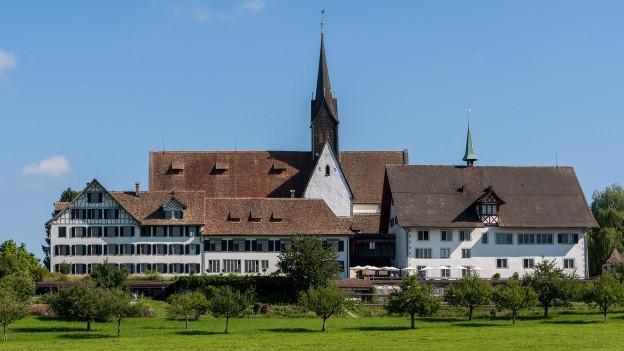 Zwei grosse Gebäude gruppieren sich um eine Kirche