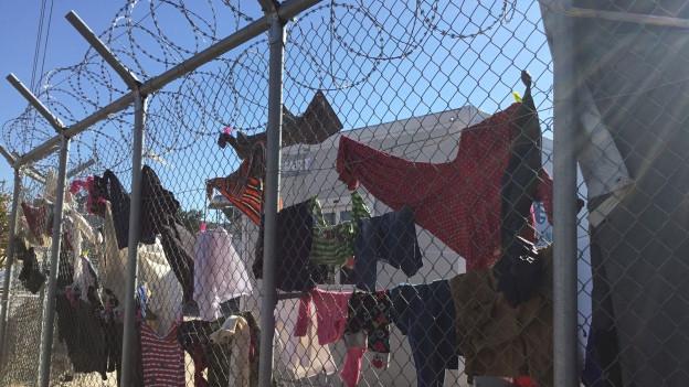 Aufgehängte Kleider an einem Zaun eines Flüchtlingcamps.