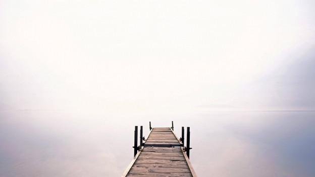 Steg im Wasser mit Gegenlicht.
