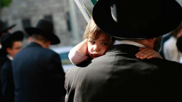 Ein Mädchen getragen von einem jüdischen Mann mit Hut.