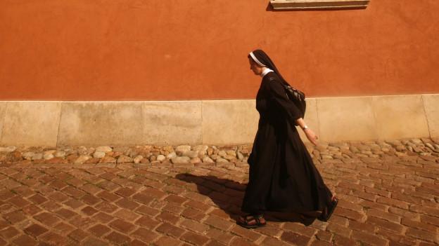 Eine Nonne läuft an einer Hauswand vorbei