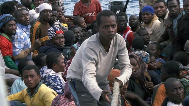 """Flüchtlinge auf einem Boot in einem Ausschnitt aus dem Film """"Eldorado""""."""