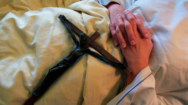 Sterbener auf eine Bett mit Kreuz.