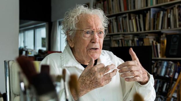 Ein älterer Mann in seinem Künstleratelier.