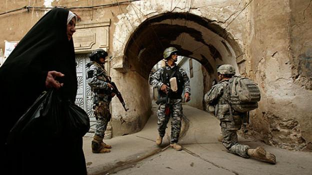 2009: Eine irakische Frau geht an US-Soldaten vorbei.