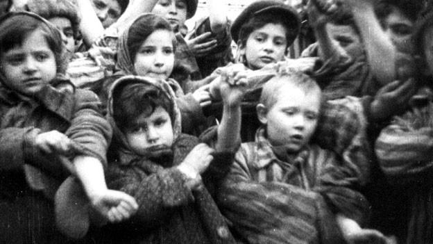 Kinder zeigen ihre Identifikationsnummern des Konzentrationslagers Auschwitz.