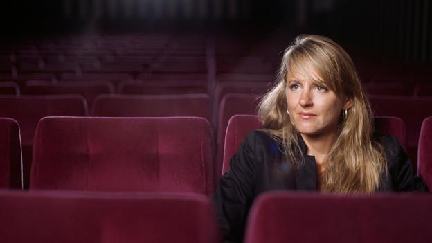 Porträt von Seraina Rohrer, die in einem leeren Kino sitzt.