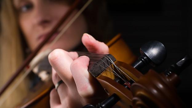 Nahaufnahme einer Hand am Geigenhals, dahinter ist die Musikerin verschwommen zu sehen