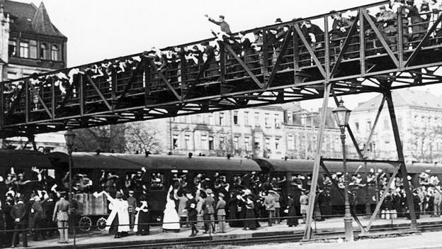 Menschenmassen stehen an einem Zug.