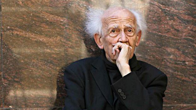 Zygmunt Bauman, ein älterer Herr mit weissem Haar und runzliger Stirn, sitzt vor einer Mauer und hält sich die Hand vor den Mund in nachdenklicher Pose.