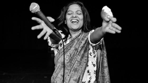 Eine schwarz-weisse Fotografie zeigt eine Frau mit schwarzen Haaren, die singend ein Mikrofon in der Hand hält.