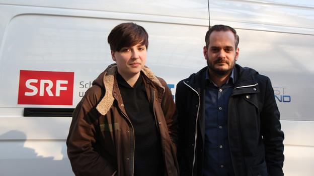 Auf dem Bild sieht man die beiden Schweizer Schriftsteller Dorothee Elmiger und Jonas Lüscher vor einem SRF-Sendewagen in Leipzig an der Buchmesse.