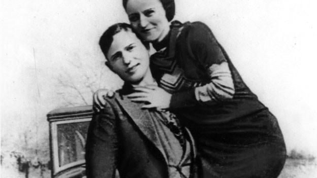 Mann hält Frau auf Arm.