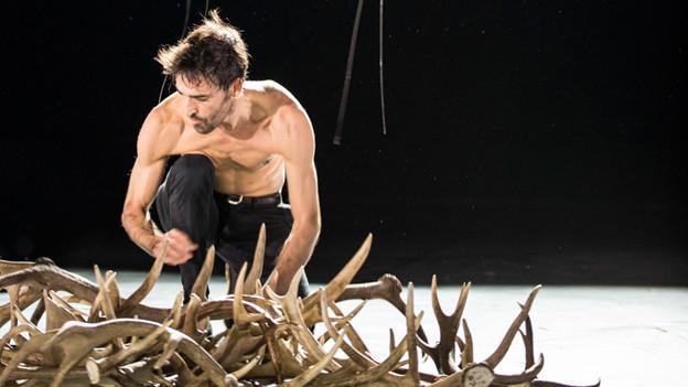 Auf der Fotografie ist eine moderne Tanz-Inszenierung zu sehen: Ein Mann mit nacktem Oberkörper beugt sich über einen Haufen Hirschgeweihe.