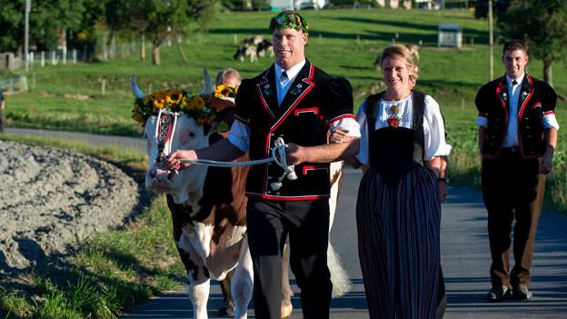 Mann und Frau in Tracht mit geschmückter Kuh.