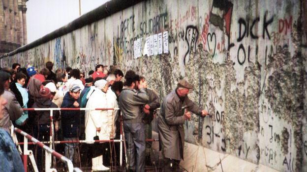 Man sieht die Berliner Mauer und Ostdeutsche, die sie zerstören möchten.