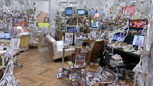 Chaotisches Büro mit vielen Bildschirmen und mit Alufolie behängten Wänden