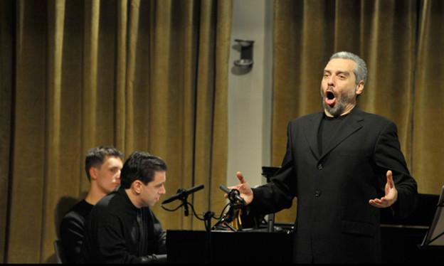 Die Fotografie zeigt einen schwarz gekleideten Sänger mit grauem Bart.