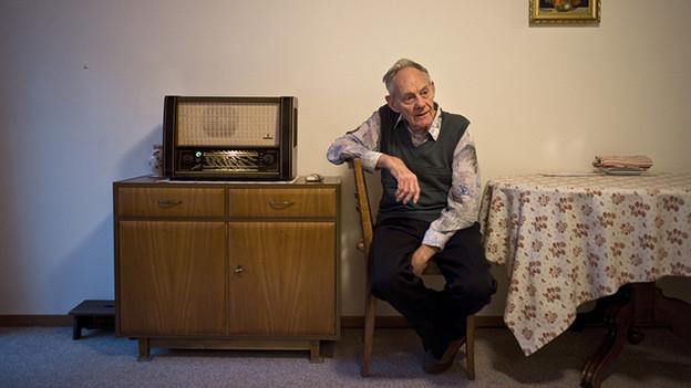 Ein älterer Mann sitzt in einer Wohnung neben einem Radio