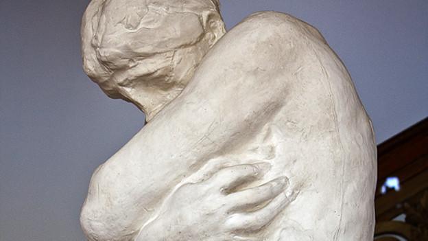 Frau bedeckt ihren Körper mit den Armen.
