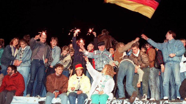 Junge Leute sitzen in der Nacht auf einer Mauer. Wunderkerzen brennen, man sieht eine Deutschland-Fahne.