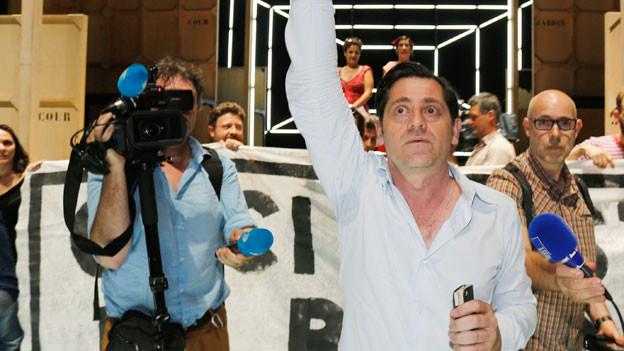 Olivier Py in weissem Hemd hebt seinen rechten Arm.