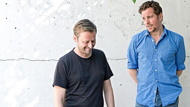 Zwei Männer posieren vor einer Wand.