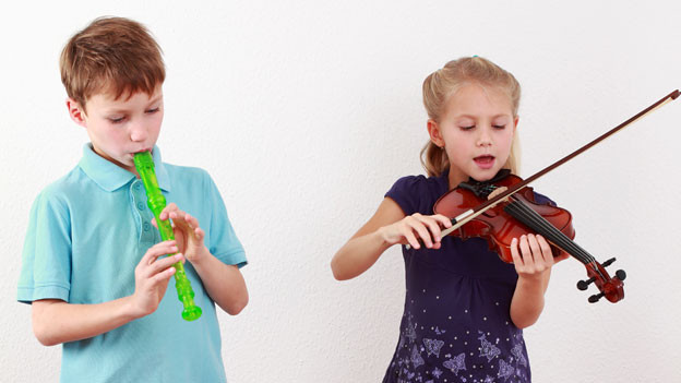 Ein Junge spielt Flöte, ein Mädchen Geige