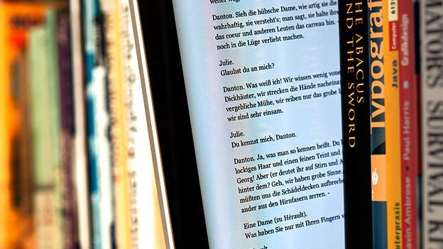 IPad mit E-Book sthet in Bücherregal.